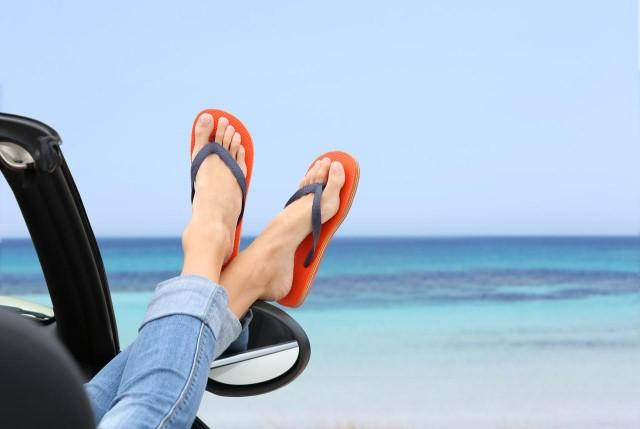 ступни в сланцах на фоне моря